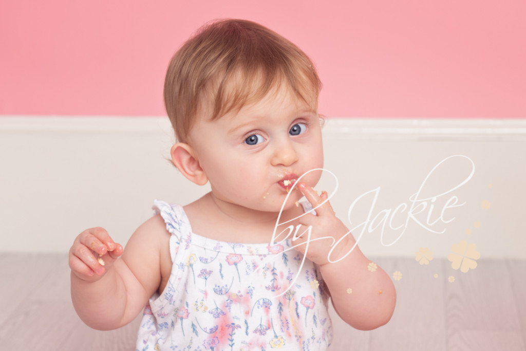 Image of 12 month old baby girl enjoying cake smash photo by Babies By Jackie Photography near Howden, York, Goole and Beverley