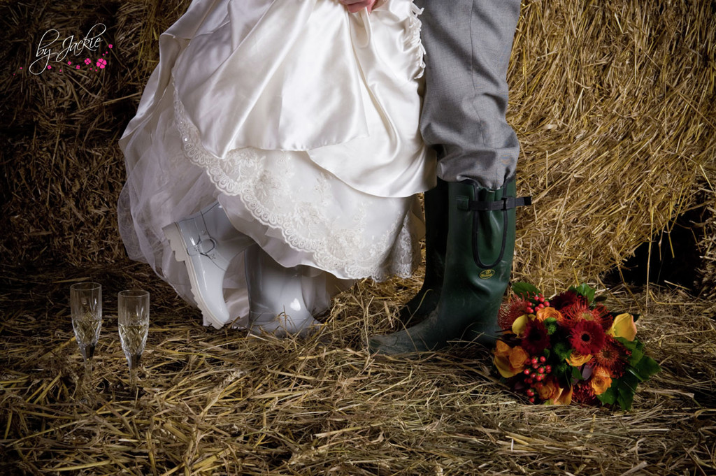 Photo of bride and groom wearing wellington boots in a barn in front of haystacks at a rural wedding in Selby, Yorkshire. Image copyright By Jackie Photography in Hemingbrough, Selby.