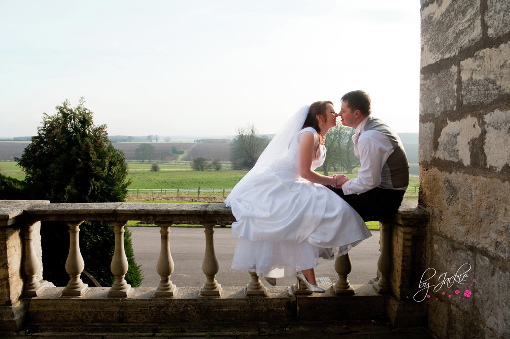 Photo of bride and groom kissing seated on a wall outside Hazlewood Castle, near York and Leeds. Image copyright By Jackie Photography, Selby