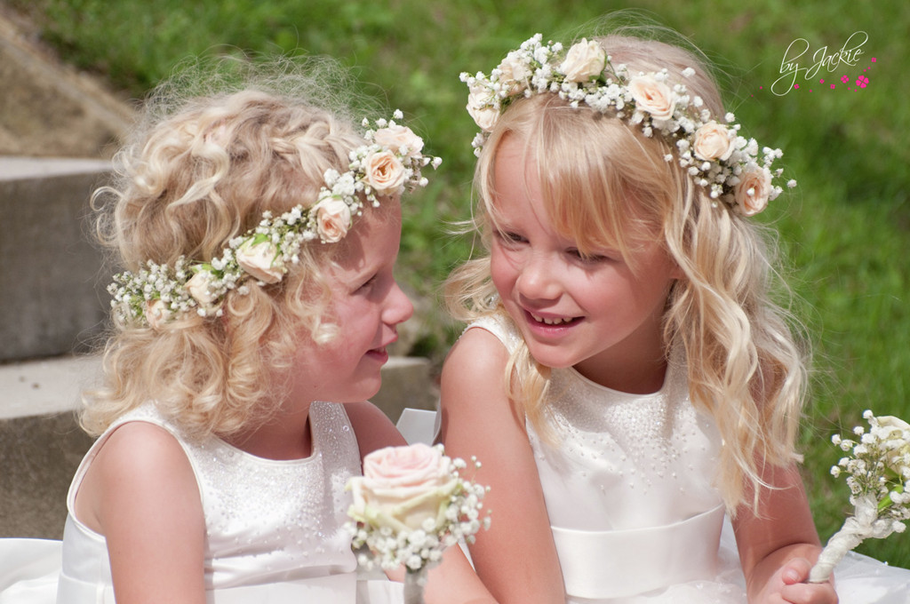 Photo of two flower girls or bridesmaids with flowers in their hair sitting on a step chatting at a wedding near Leeds. Image copyright By Jackie Photography near Howden and Goole