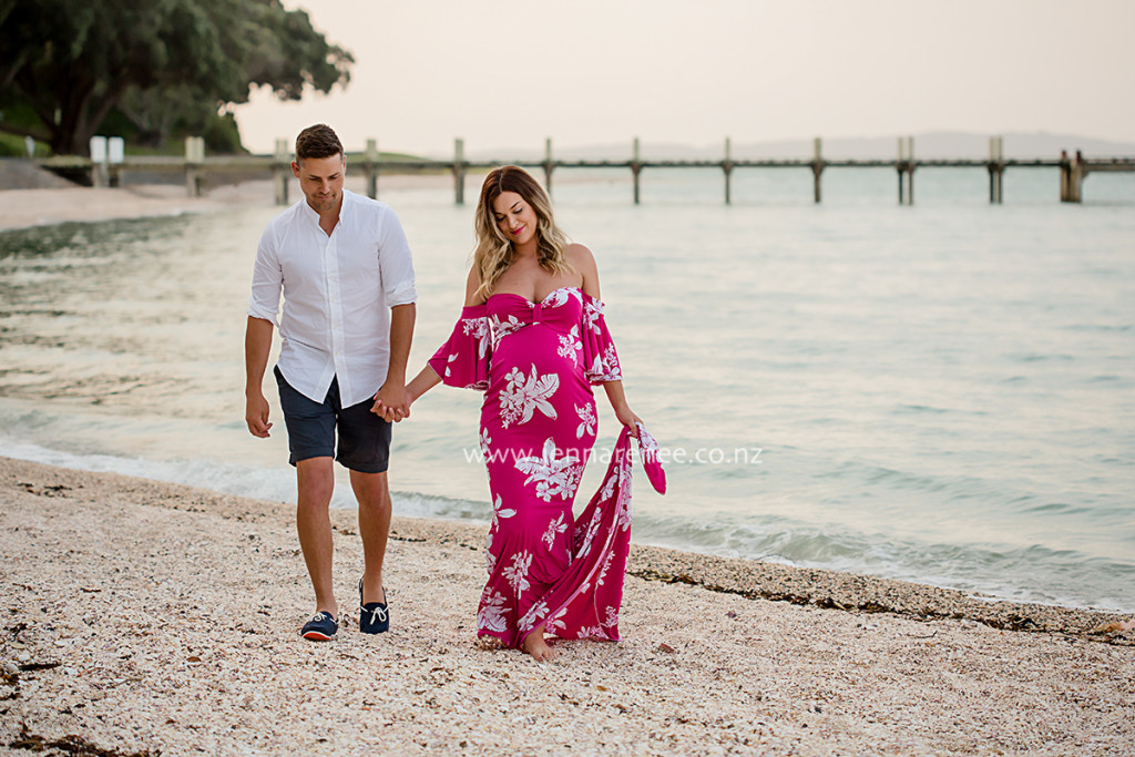maternity portrait of couple walking along the beach at sunset